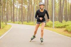 Vrouwenatleet op rolschaatsen stock afbeeldingen
