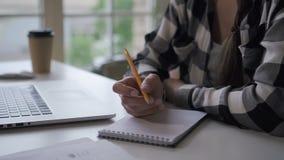 Vrouwenauteur het schrijven binnen investeert notitieboekje, die bij bureau met laptop werken in huisbureau stock videobeelden