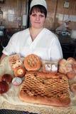 Vrouwenbakker met broodproducten in bakkerij stock afbeeldingen