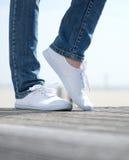 Vrouwenbenen in comfortabele witte schoenen die zich in openlucht bevinden Stock Foto