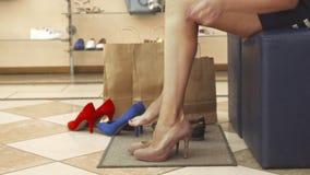 Vrouwenbenen die beige schoenen op dichte omhooggaand proberen stock footage