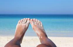 Vrouwenbenen die op de oceaankust in de zonneschijn leggen Royalty-vrije Stock Foto