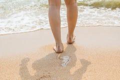 Vrouwenbenen die op het strandzand lopen stock fotografie