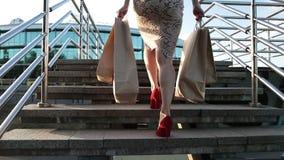 Vrouwenbenen die op treden met het winkelen zakken lopen stock video