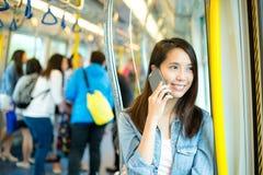 Vrouwenbespreking aan cellphone aan de gang compartiment stock fotografie