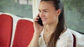 Vrouwenbespreking aan celtelefoon in het openbare vervoer, meisje die op de telefoon in de stedelijke bus spreken stock footage