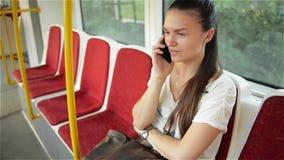 Vrouwenbespreking aan celtelefoon in het openbare vervoer, meisje die op de telefoon in de stedelijke bus spreken stock videobeelden