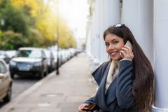 Vrouwenbesprekingen op haar mobiele telefoon op een klassieke straat van Londen stock afbeeldingen
