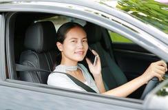Vrouwenbestuurder die haar mobiele telefoon met behulp van terwijl het drijven van auto stock fotografie