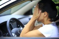 Vrouwenbestuurder droevig in auto stock fotografie