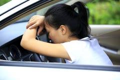 Vrouwenbestuurder droevig in auto stock foto