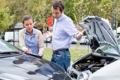 Vrouwenbestuurder en boze man die over de schade van de auto debatteren royalty-vrije stock foto's