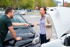 Vrouwenbestuurder en boze man die over de schade van de auto debatteren stock foto's