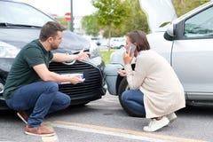 Vrouwenbestuurder en man die over de schade van de auto debatteren stock foto