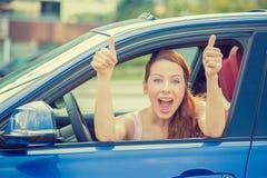 Vrouwenbestuurder het gelukkige het glimlachen beduimelt tonen omhoog het zitten binnen nieuwe auto Stock Fotografie