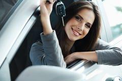 Vrouwenbestuurder Holding Car Keys die in Haar Nieuwe Auto situeren Stock Foto