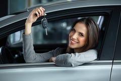 Vrouwenbestuurder Holding Car Keys die in Haar Nieuwe Auto situeren Stock Foto's
