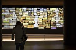 Vrouwenbezoeker die beelden nemen aan videoinstallatie bij Nationaal Stock Foto's