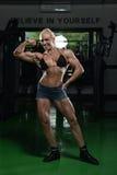 Vrouwenbodybuilder die Front Biceps Pose uitvoeren Royalty-vrije Stock Afbeeldingen