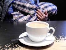 Vrouwenborst die - in de koffie met een kop die van koffie voeden zich op de lijst voor haar bevinden De concepten het drinken va stock afbeelding