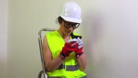 Vrouwenbouwer die smartphone gebruiken stock video