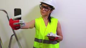 Vrouwenbouwvakker die selfies op smartphone nemen stock video
