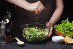 Vrouwenchef-kok in de keuken die plantaardige salade voorbereidt Het gezonde Eten Het concept van het dieet Een gezonde manier va Royalty-vrije Stock Foto
