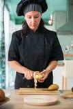 Vrouwenchef-kok die een aardappel pellen Royalty-vrije Stock Fotografie