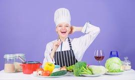 Vrouwenchef-kok die gezond voedsel koken Gastronomische hoofdgerechtrecepten Meisje in hoed en schort Heerlijk receptenconcept co stock afbeeldingen