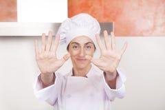 Vrouwenchef-kok die handen tonen Royalty-vrije Stock Foto's