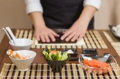 Vrouwenchef-kok klaar om Japanse sushibroodjes voor te bereiden Stock Afbeeldingen
