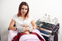 Vrouwencosmetologist geeft gezichtsmassage aan een vrouwelijke patiënt in een schoonheidssalon De kosmetiek en de routine van de  royalty-vrije stock foto's