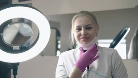 Vrouwencosmetologist stijgt masker bij geleide lamp in salon op stock footage
