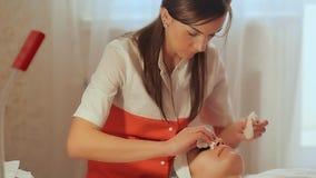 Vrouwencosmetologist veegt gezicht af afveegt Het kosmetische procedures Mechanische schoonmaken van het gezicht cosmetology stock footage