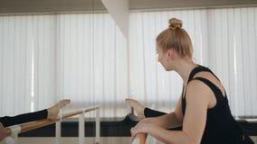 Vrouwendanser in een dansende opleidingszaal die vóór een training opwarmen De vrouwendanser breidt het been bij de staaf vooraan stock video