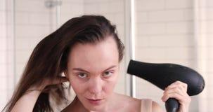 Vrouwendroogkap en het glimlachen spiegel in badkamers stock video
