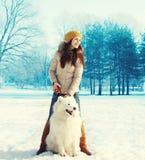 Vrouweneigenaar die met witte Samoyed-hond in de winter lopen Royalty-vrije Stock Afbeelding