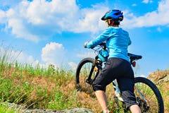 Vrouwenfietser die haar fiets naar omhoog duwen een steile helling stock afbeelding