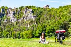 Vrouwenfietser met geladen fiets die onderbreking hebben terwijl het reizen stock afbeelding
