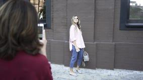 Vrouwenfotograaf die schoten van een blondemodel maken met haar telefoon stock video