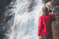 Vrouwenfotograaf die waterval van mening genieten Stock Fotografie