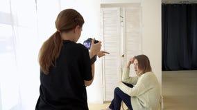 Vrouwenfotograaf en model alvorens te schieten media De fotograaf gaat met te worden model interactie aan beter geschoten romanti stock videobeelden