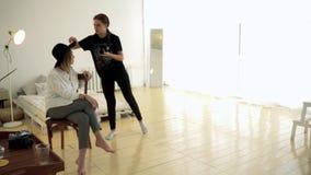 Vrouwenfotograaf en model alvorens te schieten media De fotograaf verbetert details van model alvorens beeld binnen te nemen stock videobeelden