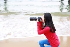 Vrouwenfotograaf in Kuststrand stock foto's