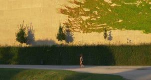 Vrouwengangen in de zomerpark met geschoren struiken stock video
