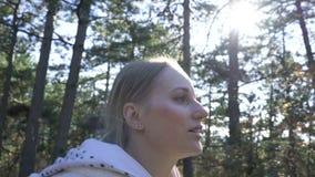 Vrouwengangen door het bos op een zonnige dag stock footage