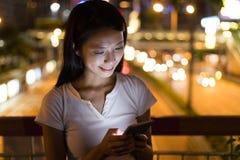 Vrouwengebruik van mobiele telefoon bij nacht Stock Foto's