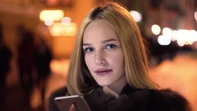 Vrouwengebruik van slimme telefoon in de de wintertijd bij nacht en glimlach stock video