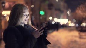 Vrouwengebruik van slimme telefoon in de de wintertijd bij nacht en glimlach stock footage