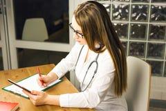 Vrouwengeneeskunde de arts schrijft voorschrift aan patiënt bij worktable Royalty-vrije Stock Afbeeldingen